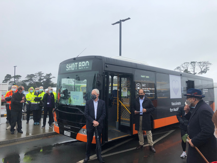 Auckland Mayor Phil Goff stands in front of one of the first vaccination buses